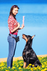 Beautiful girl playing with black doberman