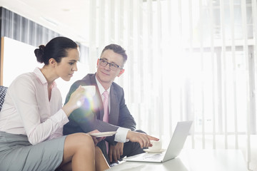 Businessman and businesswoman discussing over laptop in office