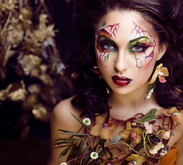beauty woman with face art and jewelry from flowers orchids