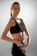 Sporty young woman with measuring tape