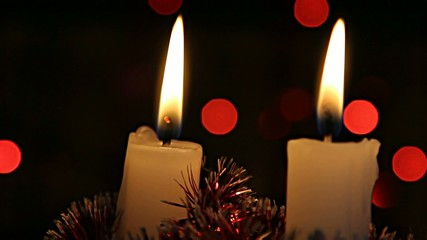 Christmas candles burning on a background of twinkling garlands
