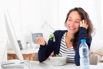 Young attractive student eating salad while phoning