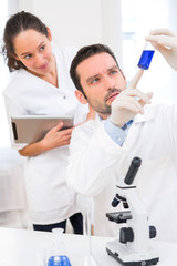 Scientist and his assistant working in a lab