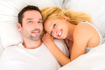Portrait of a young happy couple in a bed