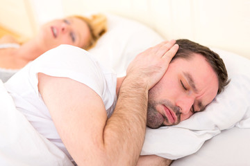 Young man can't sleep because of girlfriend's snoring