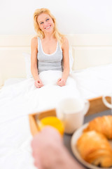 Man bringing young attractive woman breakfast in bed