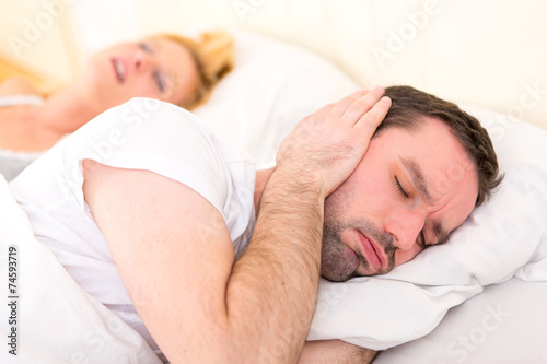 canvas print picture Young man can't sleep because of girlfriend's snoring
