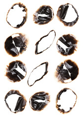 Collection of burnt holes in a piece of paper isolated on white