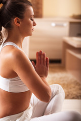 Young  woman meditate  in her living room.