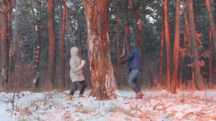 Winter couple having fun playing in snow outdoors
