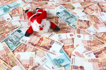 Toy Santa lying down on russian money background