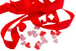 Red ribbon and confetti in the form of hearts isolated on white