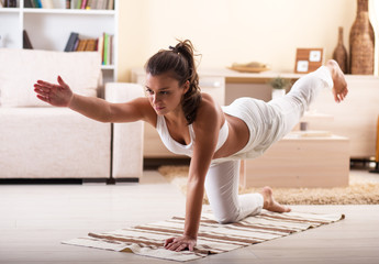 Young  woman doing yoga in her living room.