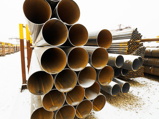 heap of steel pipes in outdoor warehouse