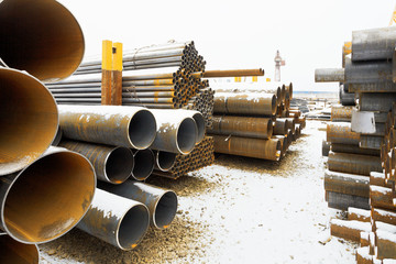 many steel pipes on outdoor warehouse