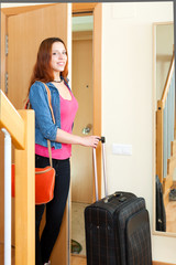 Smiling young cute female tourist with luggage near door in home