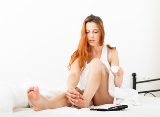 woman caring for toes with cosmetic cream
