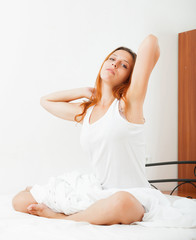 woman lying lazily on the white sheets on the bed at home