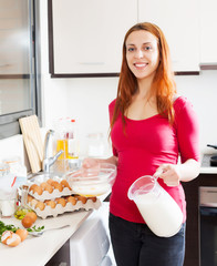 Smiling woman making scrambled eggs with milk
