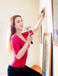 woman hanging  art picture on wall