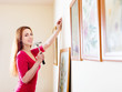 Smiling  woman hanging  art picture