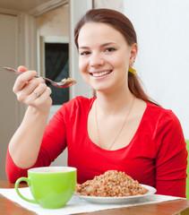 Smiling woman in red eats buckwheat porridge
