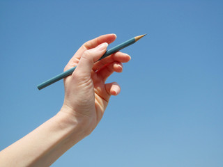 Raised hand with a wooden pen