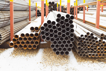 piles of metal pipes in outdoor warehouse