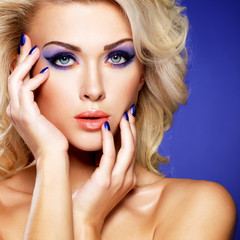 Beautiful woman with beauty purple manicure and makeup of eyes.