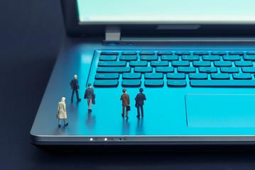 Miniature figures walking on a laptop