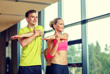 smiling man and woman exercising in gym