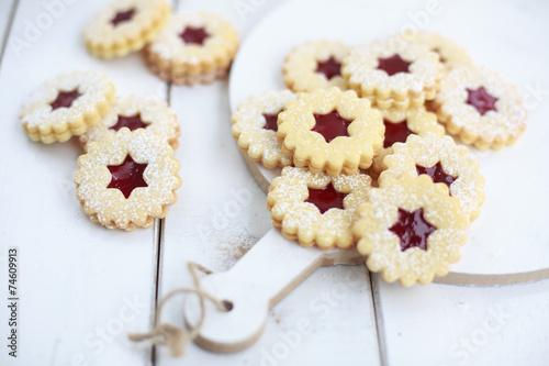 Linzer Kekse mit Himbeerkonfitüre auf einem Holztisch - 74609913