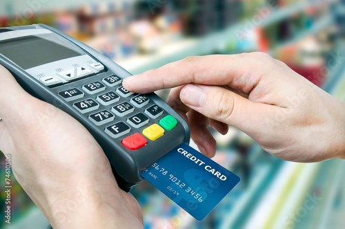 Hand with credit card swipe through terminal for sale in superma - 74610306