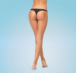 close up of female legs in black bikini panties