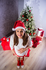 Pregnant woman standing next to Christmas tree and posing