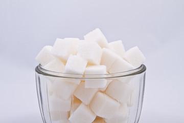 Сахар рафинад на белом фоне в прозрачном стакане
