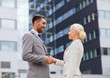 smiling businessmen standing over office building