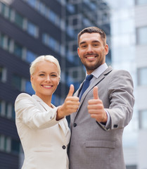 smiling businessmen showing thumbs up