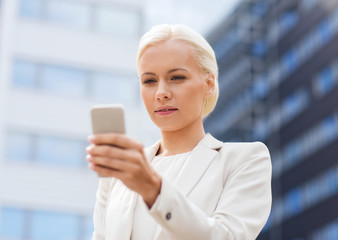 serious businesswoman with smartphone outdoors