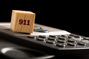 Wooden cube with 911 on a phone keyboard