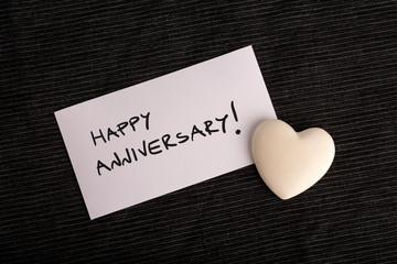 Happy anniversary handwritten on a white card