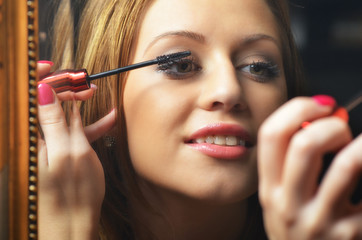 Beautiful young woman having fun while putting make up in front
