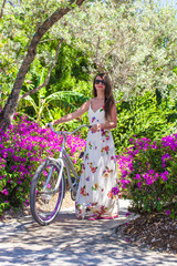 Young beautiful woman on vacation biking at lush garden