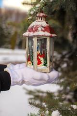 Beautiful red decorative Christmas lantern on warm mittens