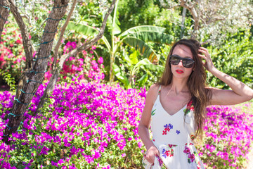 Young beautiful woman on summer vacation at lush garden