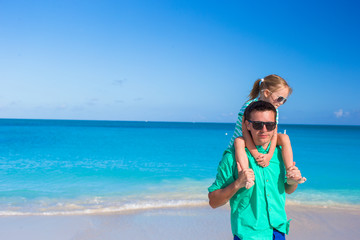 Adorable little girl have fun with dad during tropical beach