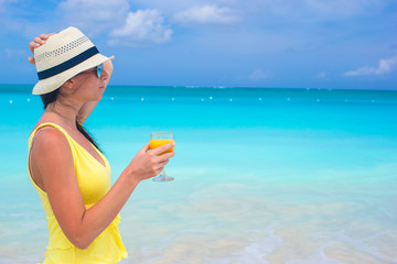 Orange juice in female hand on background of the sea