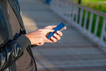 Closeup man's hands using mobile phone outdoors