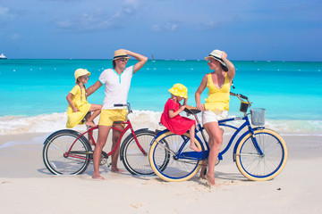 Young family of four riding bicycles on tropical sand beach