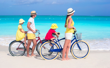 Young family with little kids ride bikes on tropical beach